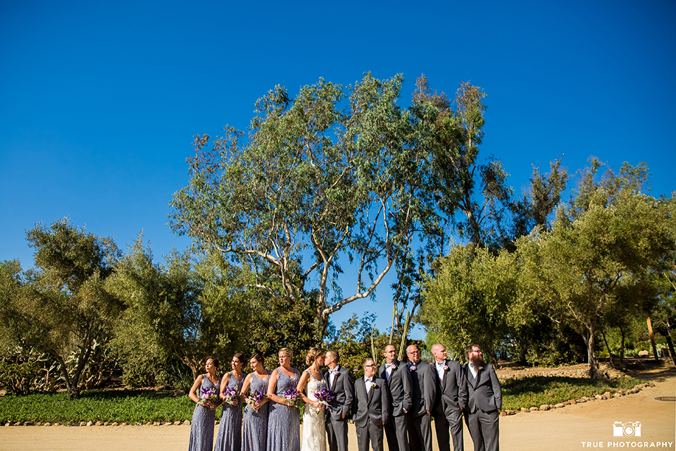 San diego outdoor wedding at leo carillo ranch bride form fitting gown with a sweetheart neckline with thin straps and beaded detail on bodice with groom charcoal grey tuxedo with a black shawl and matching vest with a white dress shirt and plaid bow tie with a white floral boutonniere with wedding party bridesmaids long lavender dresses with beading detail and groomsmen charcoal grey tuxedos with bow ties