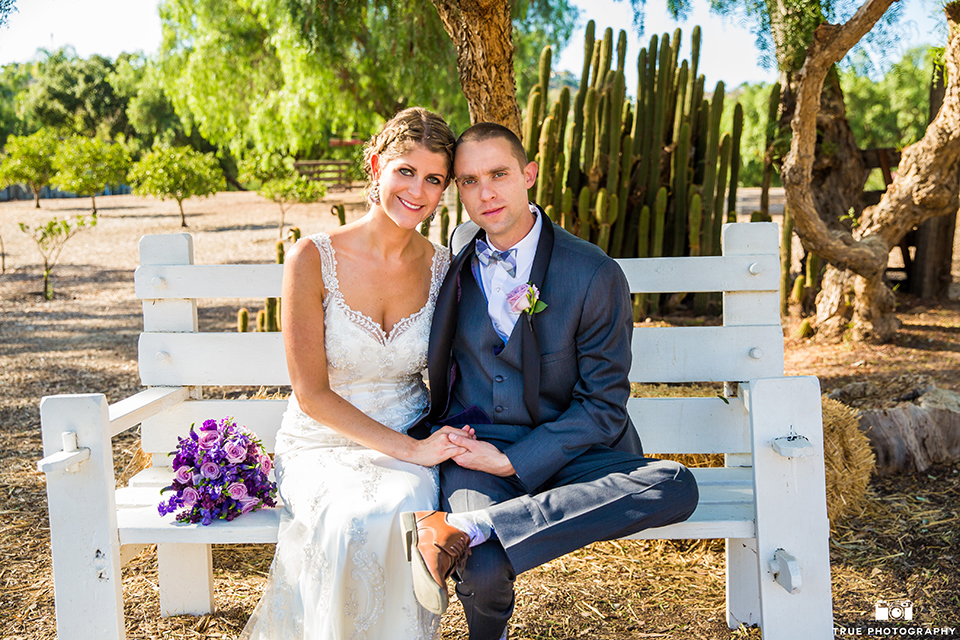 San diego outdoor wedding at leo carillo ranch bride form fitting gown with a sweetheart neckline with thin straps and beaded detail on bodice with groom charcoal grey tuxedo with a black shawl and matching vest with a white dress shirt and plaid bow tie with a white floral boutonniere sitting on bench with purple floral bridal bouquet