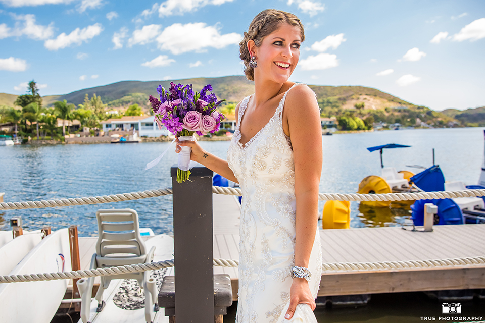 San diego outdoor wedding at leo carillo ranch bride form fitting gown with a sweetheart neckline with thin straps and beaded detail on bodice holding purple floral bridal bouquet
