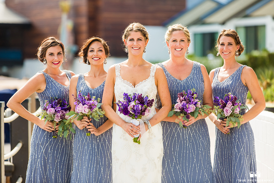 San diego outdoor wedding at leo carillo ranch bride form fitting gown with a sweetheart neckline with thin straps and beaded detail on bodice holding purple floral bridal bouquet standing with bridesmaids long lavender dresses with beaded detail holding purple floral bridal bouquets