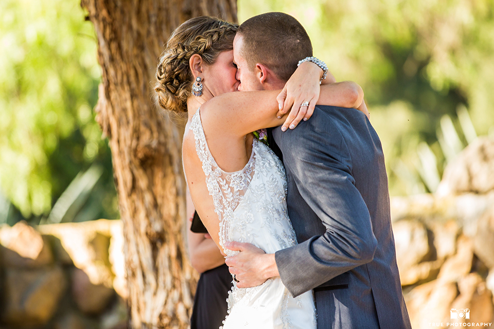 San diego outdoor wedding at leo carillo ranch bride form fitting gown with a sweetheart neckline with thin straps and beaded detail on bodice with groom charcoal grey tuxedo with a black shawl and matching vest with a white dress shirt and plaid bow tie with a white floral boutonniere kissing during ceremony