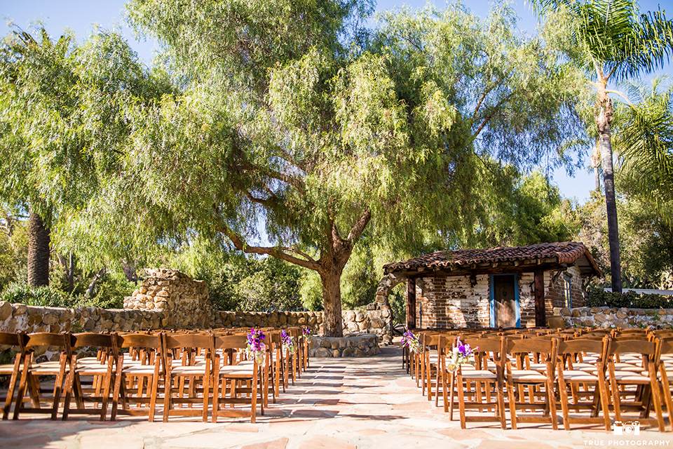 San diego outdoor wedding at leo carillo ranch ceremony set up outside with brown chairs and tree background with purple flower decor wedding photo idea for ceremony