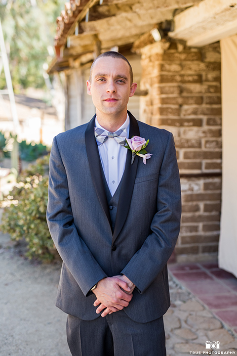 San diego outdoor wedding at leo carillo ranch groom charcoal grey tuxedo with a black shawl lapel and matching vest with a white dress shirt and purple plaid bow tie with a light purple floral boutonniere standing