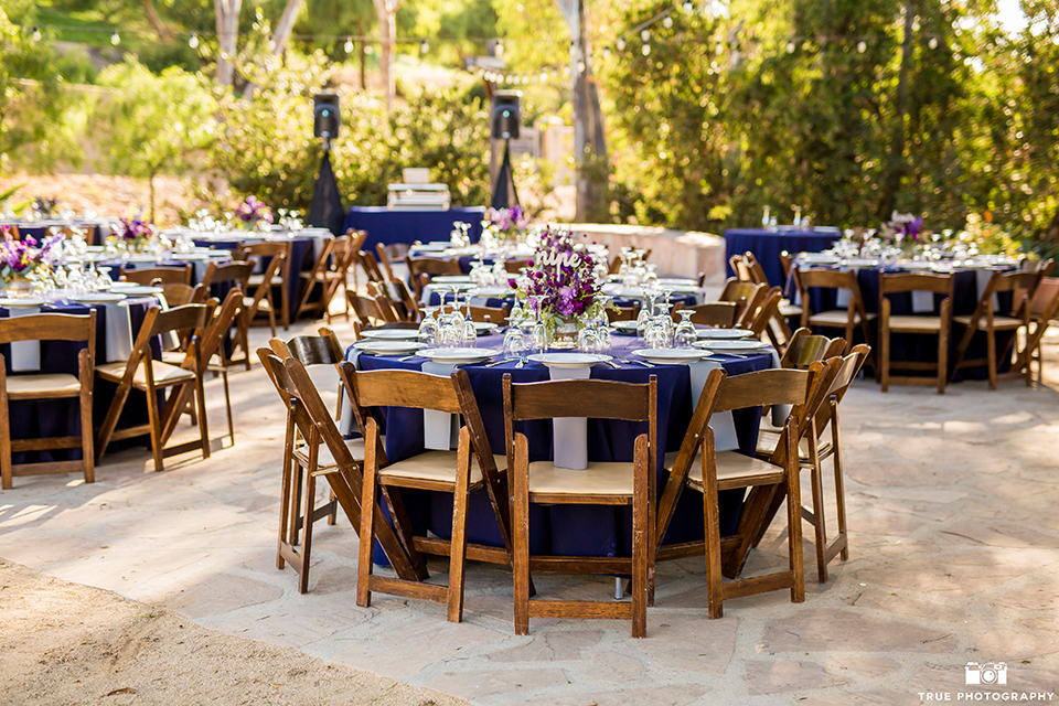 San diego outdoor wedding at leo carillo ranch reception table set up with purple linen and brown chairs with white place settings and light purple napkin decor with purple flower centerpiece decor