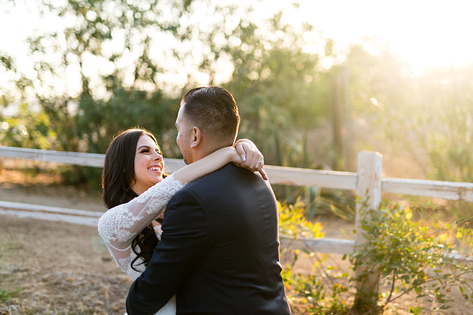 Temecula outdoor wedding at bella gardens estates bride lace ball gown with long sleeves and a sweetheart neckline with a tulle skirt and groom navy shawl lapel tuxedo with a matching vest and long navy blue tie with a white floral boutonniere hugging and smiling