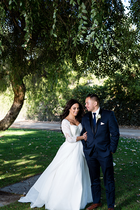 Temecula outdoor wedding at bella gardens estates bride lace ball gown with long sleeves and a sweetheart neckline with a tulle skirt and groom navy shawl lapel tuxedo with a matching vest and long navy blue tie with a white floral boutonniere standing and hugging