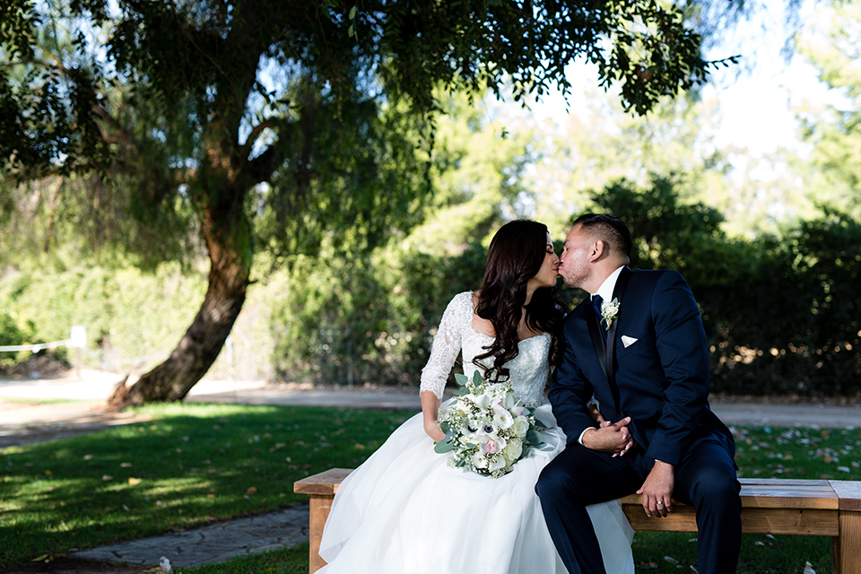 Temecula outdoor wedding at bella gardens estates bride lace ball gown with long sleeves and a sweetheart neckline with a tulle skirt and groom navy shawl lapel tuxedo with a matching vest and long navy blue tie with a white floral boutonniere sitting and kissing on bench holding white and green floral bridal bouquet