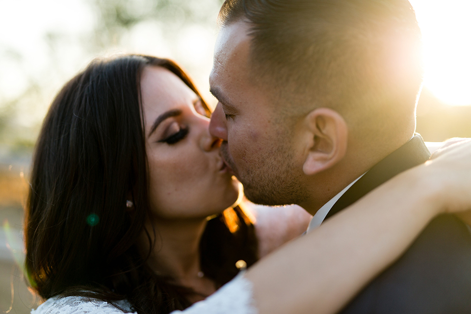 Temecula outdoor wedding at bella gardens estates bride lace ball gown with long sleeves and a sweetheart neckline with a tulle skirt and groom navy shawl lapel tuxedo with a matching vest and long navy blue tie with a white floral boutonniere kissing close up