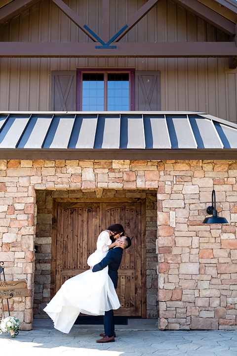 Temecula outdoor wedding at bella gardens estates bride lace ball gown with long sleeves and a sweetheart neckline with a tulle skirt and groom navy shawl lapel tuxedo with a matching vest and long navy blue tie with a white floral boutonniere hugging and kissing