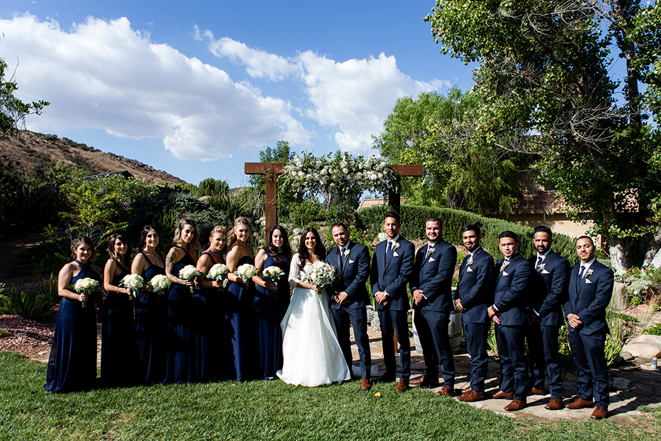 Temecula outdoor wedding at bella gardens estates bride lace ball gown with long sleeves and a sweetheart neckline with a tulle skirt and groom navy shawl lapel tuxedo with a matching vest and long navy blue tie with a white floral boutonniere with wedding party bridesmaids long blue dresses and groomsmen navy tuxedos with long ties
