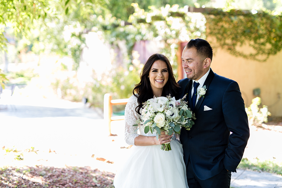 Temecula outdoor wedding at bella gardens estates bride lace ball gown with long sleeves and a sweetheart neckline with a tulle skirt and groom navy shawl lapel tuxedo with a matching vest and long navy blue tie with a white floral boutonniere hugging and bride holding white and green floral bridal bouquet