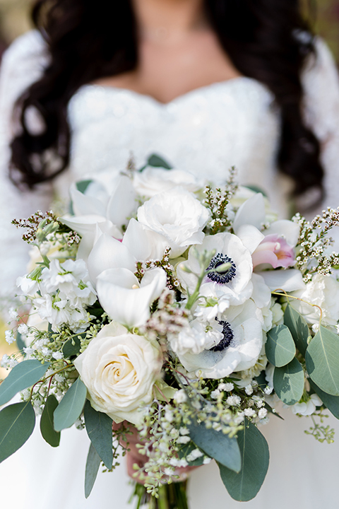 Temecula outdoor wedding at bella gardens estates bride lace ball gown with long sleeves and a sweetheart neckline with a tulle skirt holding white and green floral bridal bouquet close up