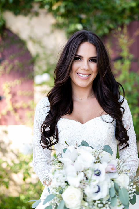Temecula outdoor wedding at bella gardens estates bride lace ball gown with long sleeves and a sweetheart neckline with a tulle skirt holding white and green floral bridal bouquet