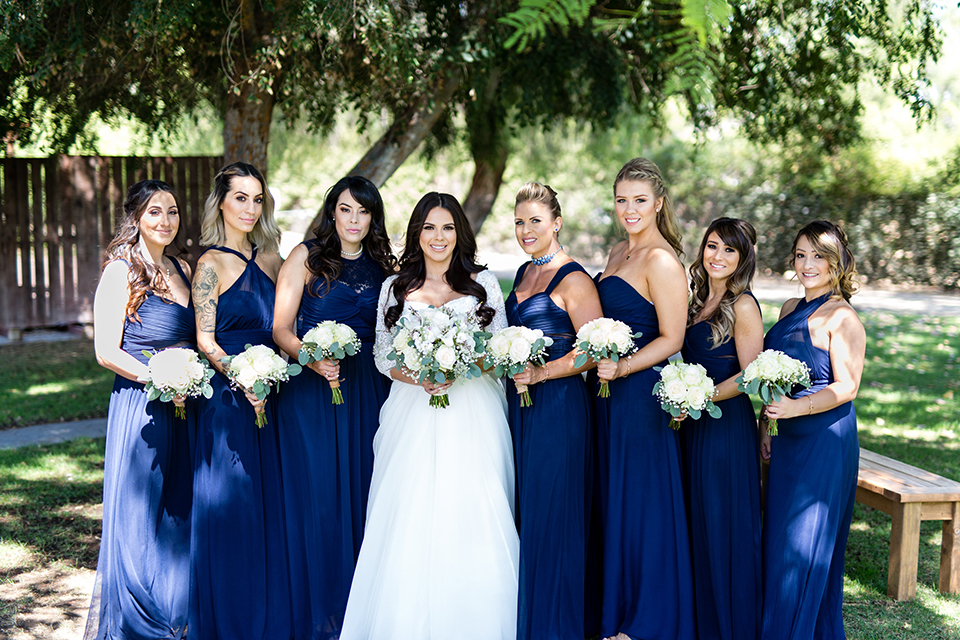 Temecula outdoor wedding at bella gardens estates bride lace ball gown with long sleeves and a sweetheart neckline with a tulle skirt holding white and green floral bridal bouquet with bridesmaids long navy dresses with white floral bridal bouquets