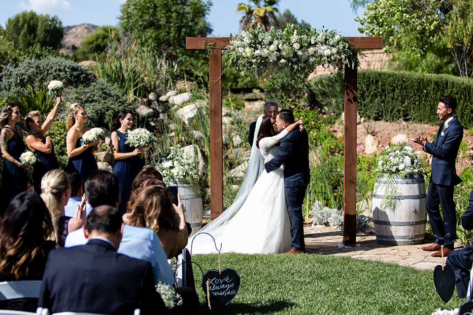 Temecula outdoor wedding at bella gardens estates bride lace ball gown with long sleeves and a sweetheart neckline with a tulle skirt and groom navy shawl lapel tuxedo with a matching vest and long navy blue tie with a white floral boutonniere kissing during ceremony