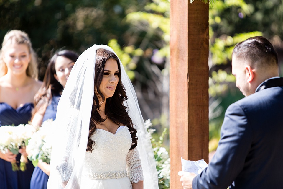Temecula outdoor wedding at bella gardens estates bride lace ball gown with long sleeves and a sweetheart neckline with a tulle skirt and groom navy shawl lapel tuxedo with a matching vest and long navy blue tie with a white floral boutonniere smiling and holding hands during ceremony