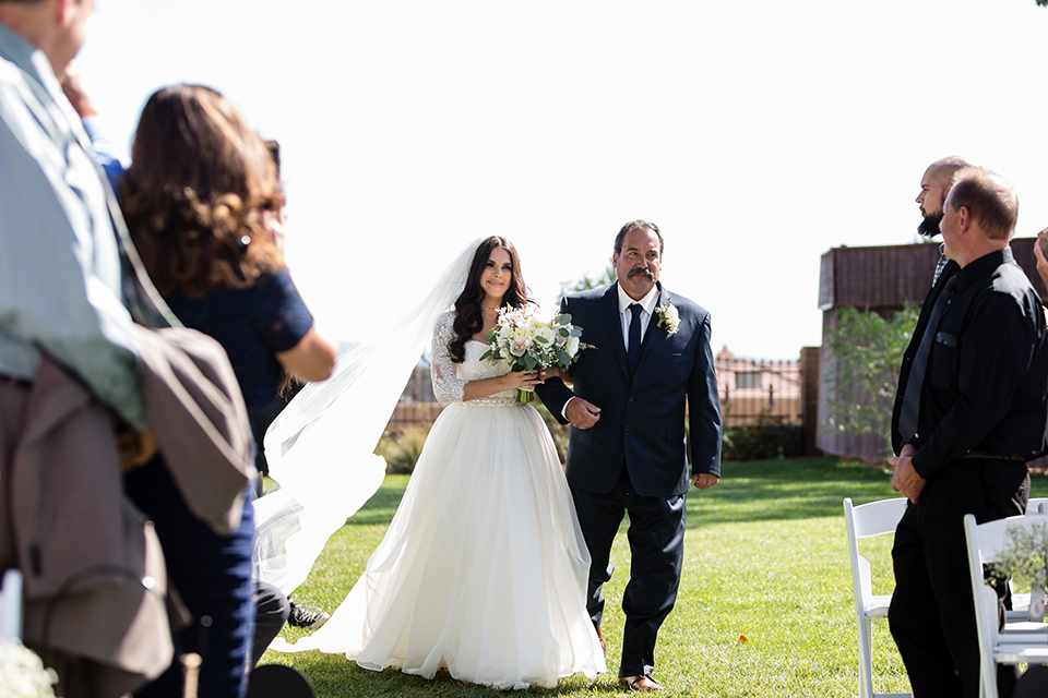 Temecula outdoor wedding at bella gardens estates bride lace ball gown with long sleeves and a sweetheart neckline with a tulle skirt holding white and green floral bridal bouquet walking down the aisle with dad