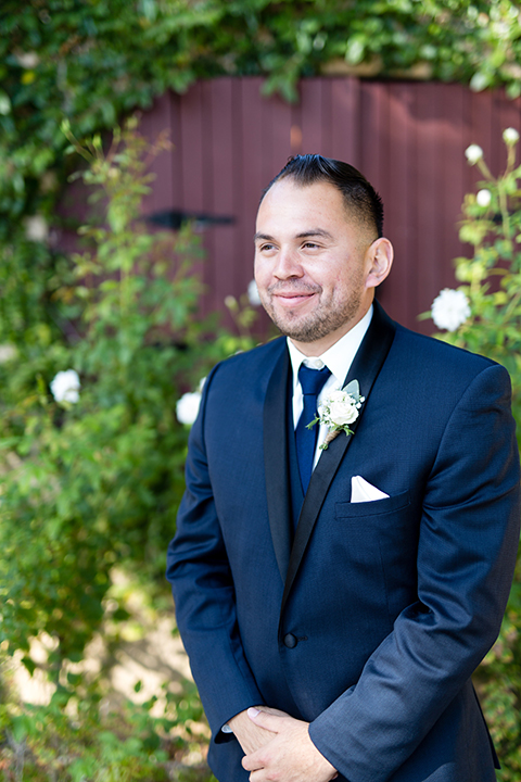 Temecula outdoor wedding at bella gardens estates groom navy shawl lapel tuxedo with a matching vest and white dress shirt with a long navy blue tie and white floral boutonniere smiling