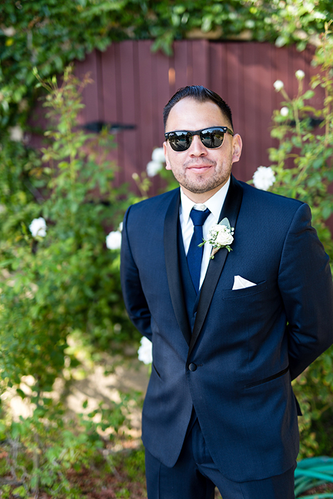Temecula outdoor wedding at bella gardens estates groom navy shawl lapel tuxedo with a matching vest and white dress shirt with a long navy blue tie and white floral boutonniere wearing sunglasses
