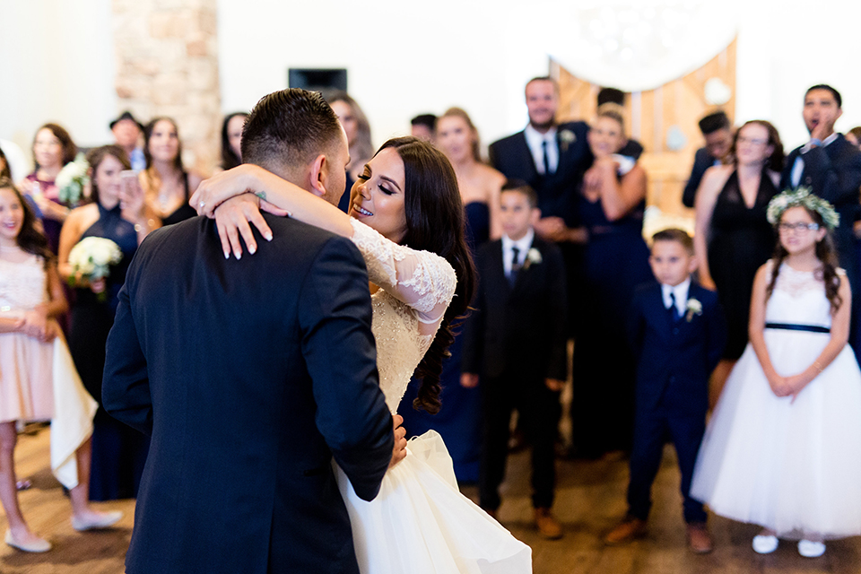 Temecula outdoor wedding at bella gardens estates bride lace ball gown with long sleeves and a sweetheart neckline with a tulle skirt and groom navy shawl lapel tuxedo with a matching vest and long navy blue tie with a white floral boutonniere first dance at reception