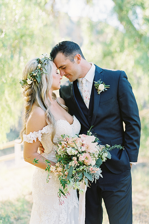 California outdoor wedding at the rancho san antonio bride form fitting lace gown with off the shoulder straps and a sweetheart neckline with a flower crown and groom navy notch lapel suit with a matching vest and white dress shirt with a long white and pink floral tie with a white floral boutonniere hugging bride holding white and green floral bridal bouquet