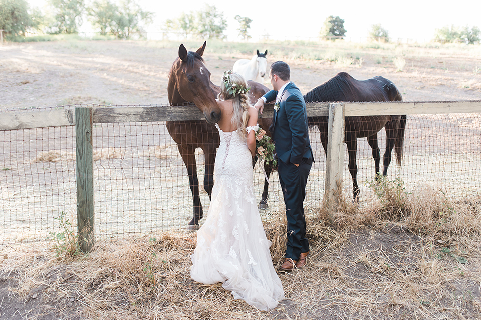 California outdoor wedding at the rancho san antonio bride form fitting lace gown with off the shoulder straps and a sweetheart neckline with a flower crown and groom navy notch lapel suit with a matching vest and white dress shirt with a long white and pink floral tie with a white floral boutonniere standing by horse bride holding white and green floral bridal bouquet