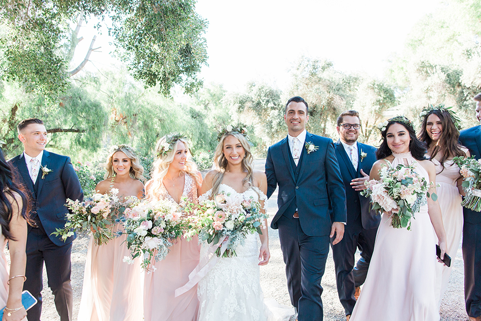 California outdoor wedding at the rancho san antonio bride form fitting lace gown with off the shoulder straps and a sweetheart neckline with a flower crown and groom navy notch lapel suit with a matching vest and white dress shirt with a long white and pink floral tie with a white floral boutonniere walking with wedding party bridesmaids long blush pink dresses and groomsmen navy suits with long floral ties