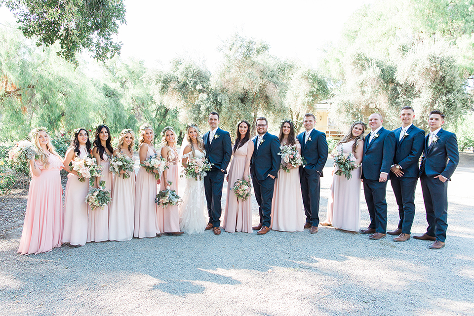 California outdoor wedding at the rancho san antonio bride form fitting lace gown with off the shoulder straps and a sweetheart neckline with a flower crown and groom navy notch lapel suit with a matching vest and white dress shirt with a long white and pink floral tie with a white floral boutonniere standing with wedding party bridesmaids long blush pink dresses and groomsmen navy blue suits with long floral ties