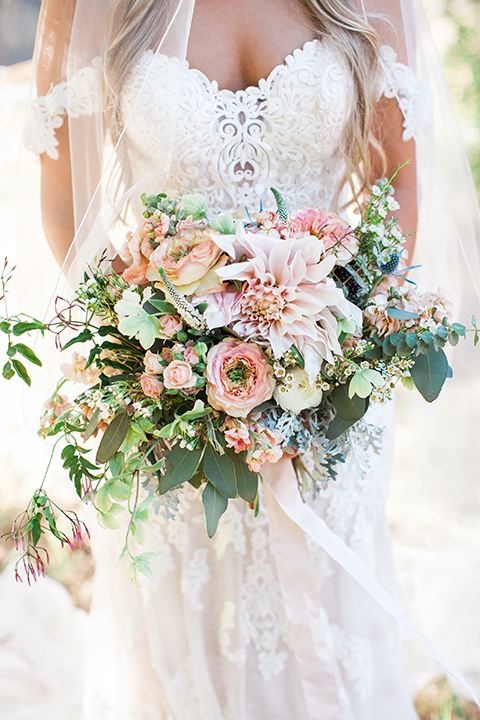 California outdoor wedding at the rancho san antonio bride form fitting lace gown with off the shoulder straps and a sweetheart neckline with a flower crown holding white and green floral bridal bouquet close up