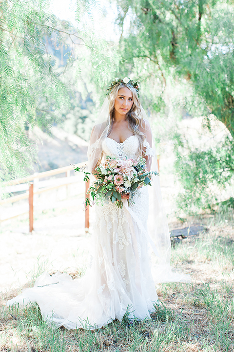 California outdoor wedding at the rancho san antonio bride form fitting lace gown with off the shoulder straps and a sweetheart neckline with a flower crown holding white and green floral bridal bouquet
