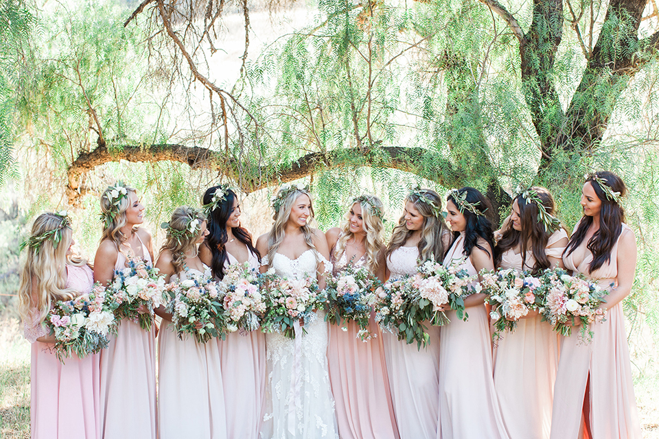 California outdoor wedding at the rancho san antonio bride form fitting lace gown with off the shoulder straps and a sweetheart neckline with a flower crown holding white and green floral bridal bouquet standing with bridesmaids long blush pink dresses and white floral bouquets