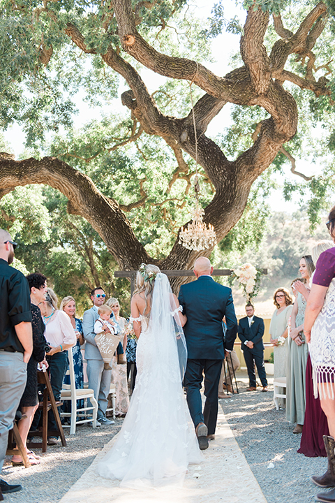 California outdoor wedding at the rancho san antonio bride form fitting lace gown with off the shoulder straps and a sweetheart neckline with a flower crown holding white and green floral bridal bouquet walking down the aisle with dad holding white and green floral bridal bouquet