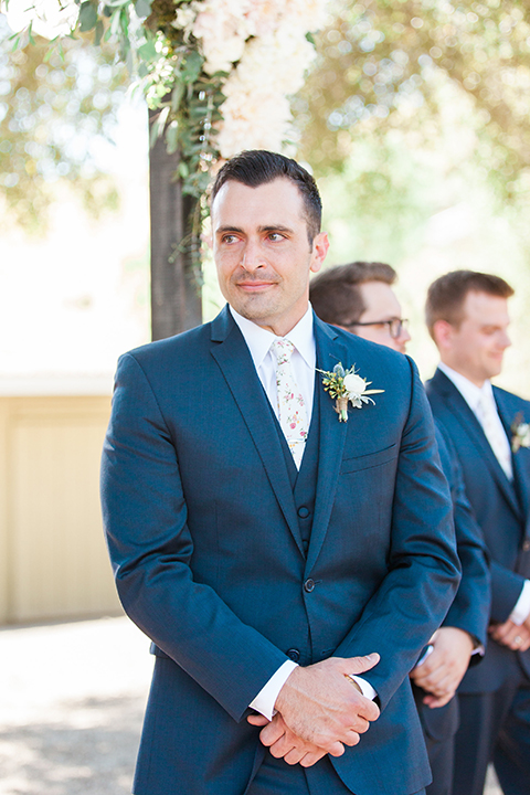 California outdoor wedding at the rancho san antonio groom navy notch lapel suit with a matching vest and white dress shirt with a long white and pink floral tie with a white floral boutonniere watching bride walk down the aisle during ceremony