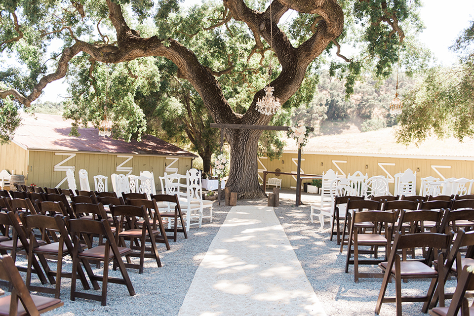 California outdoor wedding at the rancho san antonio ceremony set up white linen runner with brown and white chairs and brown wood altar with flower decor and hanging chandelier wedding photo idea for ceremony set up