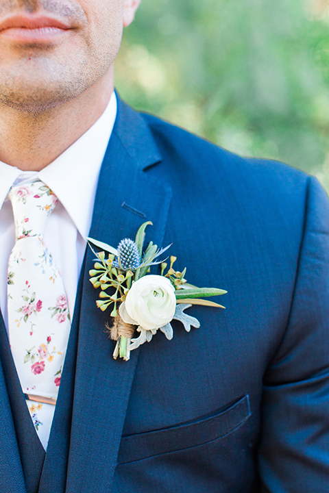 California outdoor wedding at the rancho san antonio groom navy notch lapel suit with a matching vest and white dress shirt with a long white and pink floral tie with a white floral boutonniere close up