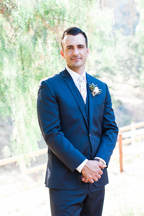 California outdoor wedding at the rancho san antonio groom navy notch lapel suit with a matching vest and white dress shirt with a long white and pink floral tie with a white floral boutonniere standing with hands folded
