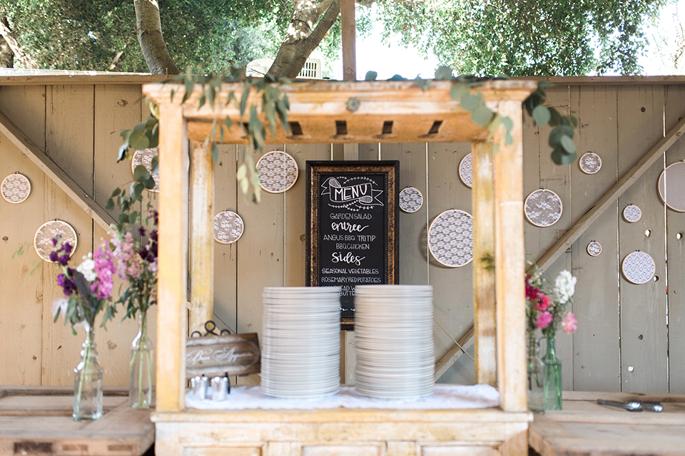 California outdoor wedding at the rancho san antonio wedding reception dinner set up with plates and black and white board for menu with wood decor and handing designs on wall with white flowers wedding photo idea for reception
