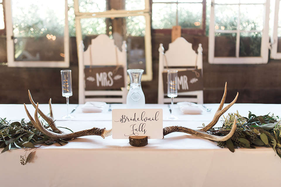 California outdoor wedding at the rancho san antonio reception decor white sweetheart table with animal decor and white chairs with brown wood mr and mrs signs with white place settings and table number wedding photo idea for reception