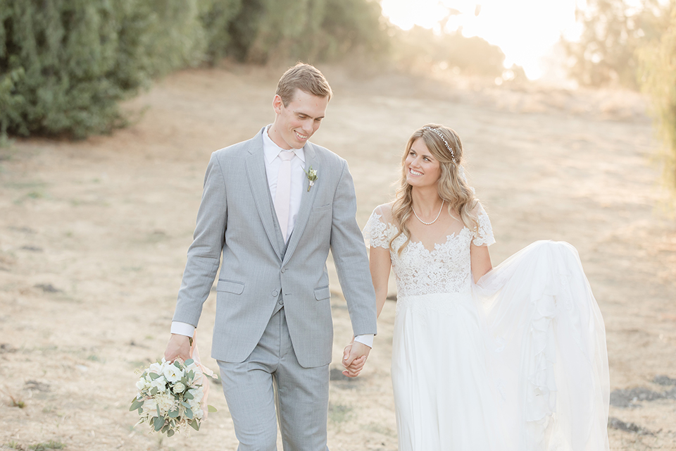 Rancho palos verdes outdoor wedding at a private estate bride a line chiffon gown with a lace bodice and short lace sleeves with a sweetheart neckline and groom heather grey notch lapel suit with a matching vest and white dress shirt with a long white tie holding hands and walking
