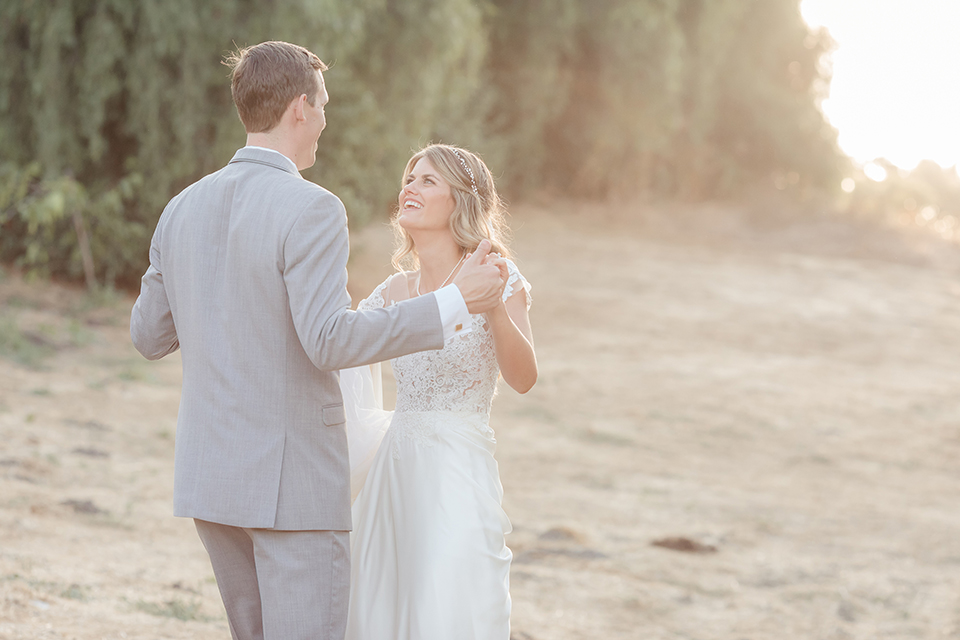 Rancho palos verdes outdoor wedding at a private estate bride a line chiffon gown with a lace bodice and short lace sleeves with a sweetheart neckline and groom heather grey notch lapel suit with a matching vest and white dress shirt with a long white tie holding hands and smiling