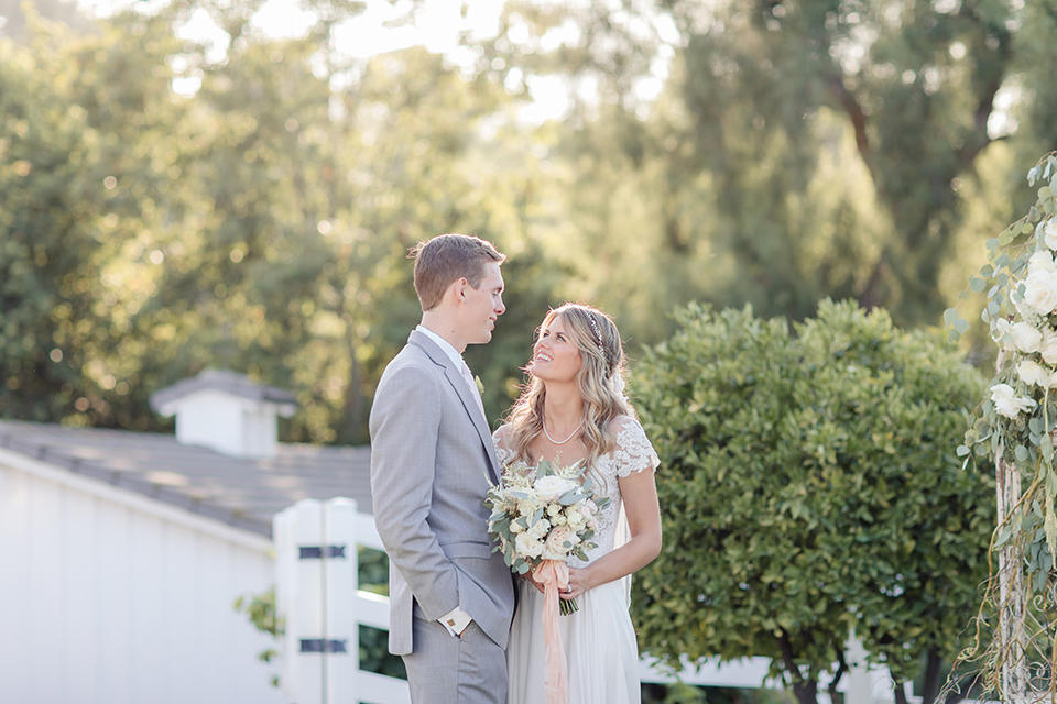 Rancho palos verdes outdoor wedding at a private estate bride a line chiffon gown with a lace bodice and short lace sleeves with a sweetheart neckline and groom heather grey notch lapel suit with a matching vest and white dress shirt with a long white tie hugging and bride holding white and green floral bridal bouquet