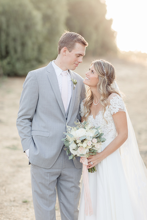 Rancho palos verdes outdoor wedding at a private estate bride a line chiffon gown with a lace bodice and short lace sleeves with a sweetheart neckline and groom heather grey notch lapel suit with a matching vest and white dress shirt with a long white tie hugging and smiling bride holding white and green floral bridal bouquet