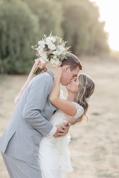 Rancho palos verdes outdoor wedding at a private estate bride a line chiffon gown with a lace bodice and short lace sleeves with a sweetheart neckline and groom heather grey notch lapel suit with a matching vest and white dress shirt with a long white tie hugging and kissing bride holding white and green floral bridal bouquet