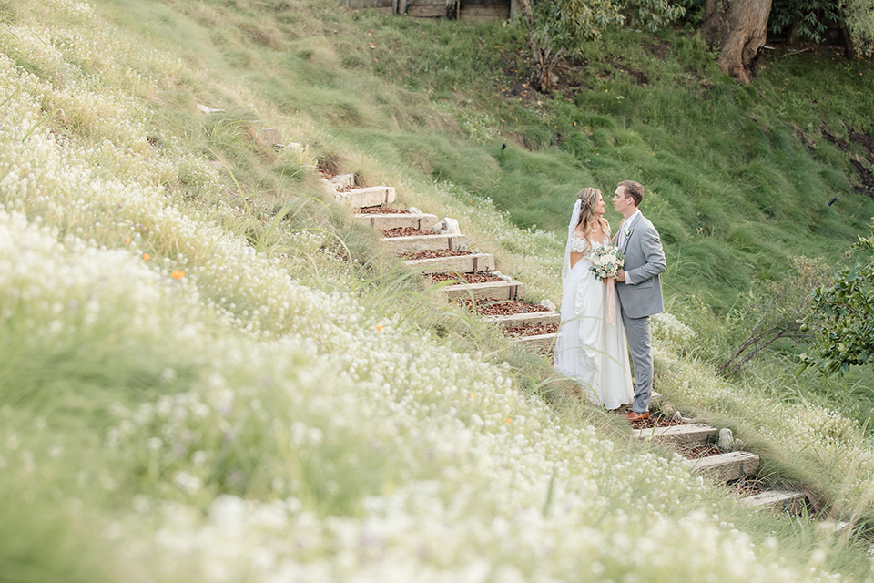 Rancho palos verdes outdoor wedding at a private estate bride a line chiffon gown with a lace bodice and short lace sleeves with a sweetheart neckline and groom heather grey notch lapel suit with a matching vest and white dress shirt with a long white tie hugging far away bride holding white and green floral bridal bouquet