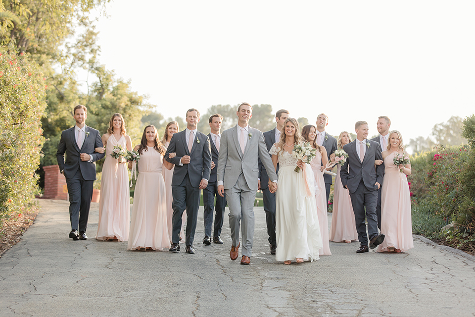 Rancho palos verdes outdoor wedding at a private estate bride a line chiffon gown with a lace bodice and short lace sleeves with a sweetheart neckline and groom heather grey notch lapel suit with a matching vest and white dress shirt with a long white tie holding hands and walking with wedding party bridesmaids long blush pink dresses and groomsmen charcoal grey suits with long white ties