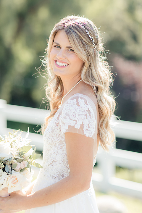 Rancho palos verdes outdoor wedding at a private estate bride a line chiffon gown with a lace bodice and short lace sleeves with a sweetheart neckline holding white and green floral bridal bouquet close up
