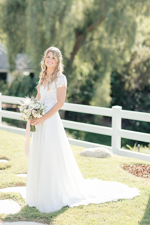 Rancho palos verdes outdoor wedding at a private estate bride a line chiffon gown with a lace bodice and short lace sleeves with a sweetheart neckline holding white and green floral bridal bouquet