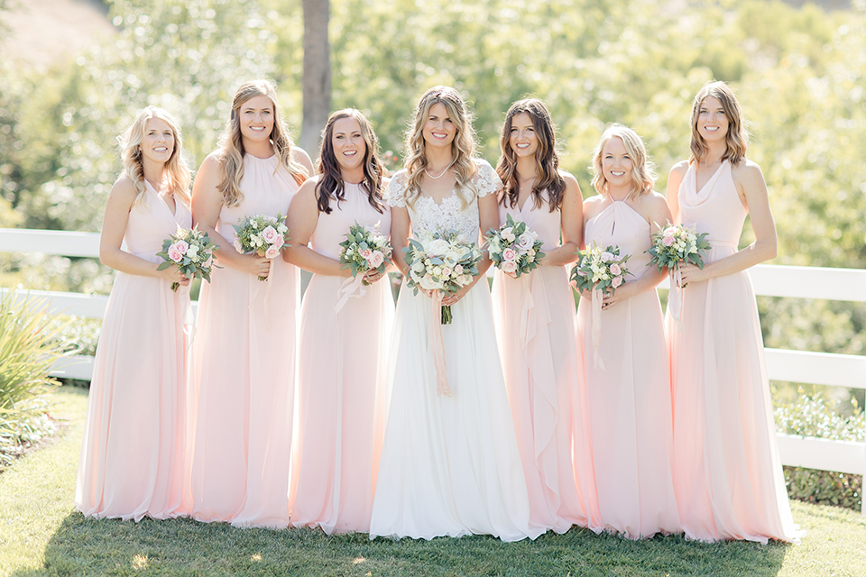Rancho palos verdes outdoor wedding at a private estate bride a line chiffon gown with a lace bodice and short lace sleeves with a sweetheart neckline holding white and green floral bridal bouquet with bridesmaids long blush pink dresses holding white and green floral bridal bouquets