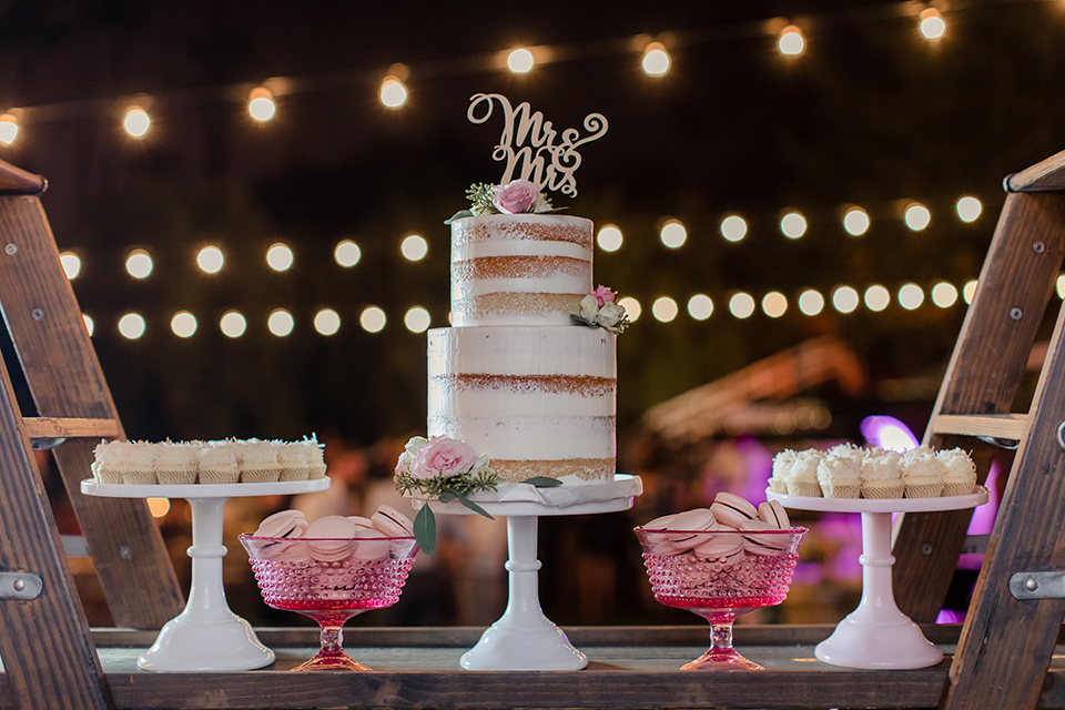 Rancho palos verdes outdoor wedding at a private estate wedding cake two tier white naked cake with gold mr and mrs cake topper with assortment of desserts on white trays wedding photo idea for cake