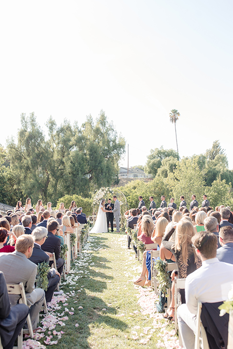 Rancho palos verdes outdoor wedding at a private estate bride a line chiffon gown with a lace bodice and short lace sleeves with a sweetheart neckline and groom heather grey notch lapel suit with a matching vest and white dress shirt with a long white tie holding hands during ceremony far away
